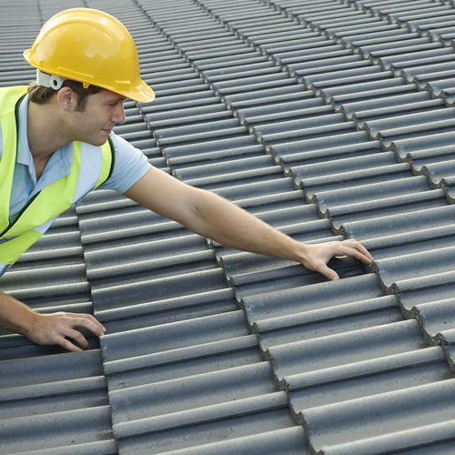 A Roofer Inspects Tiles