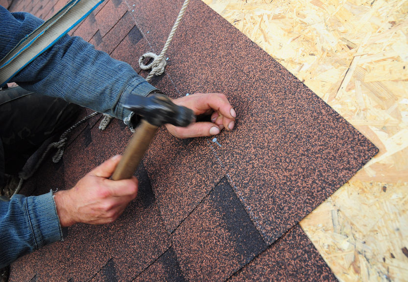 roofer installing asphalt roof shingles