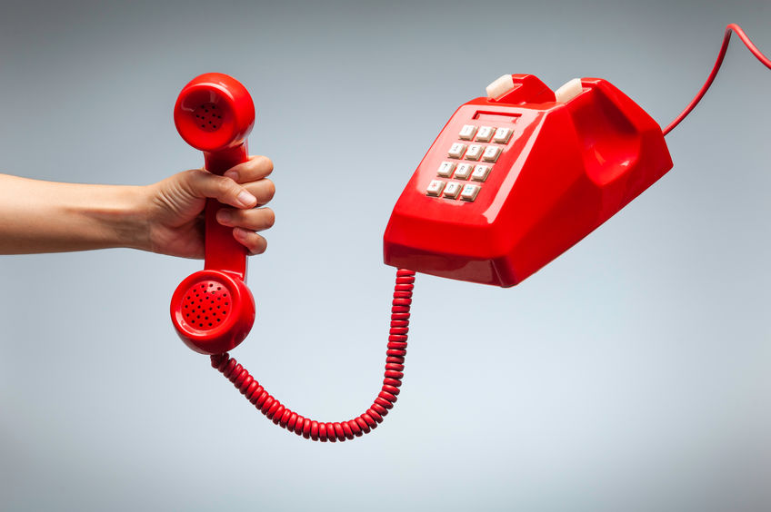 Hand holding telephone, classic red telephone receiver