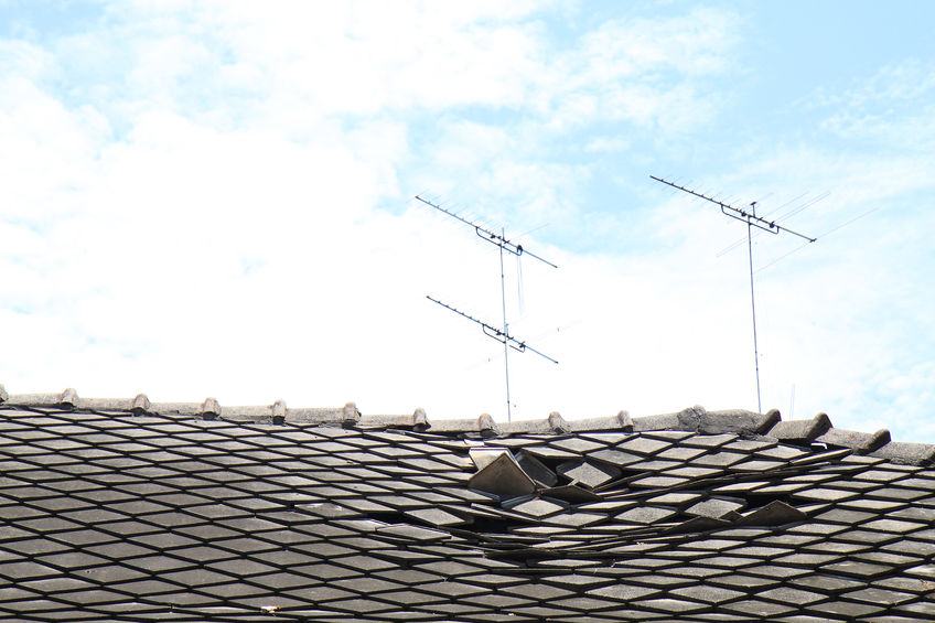 Broken roof shingles with blue sky background